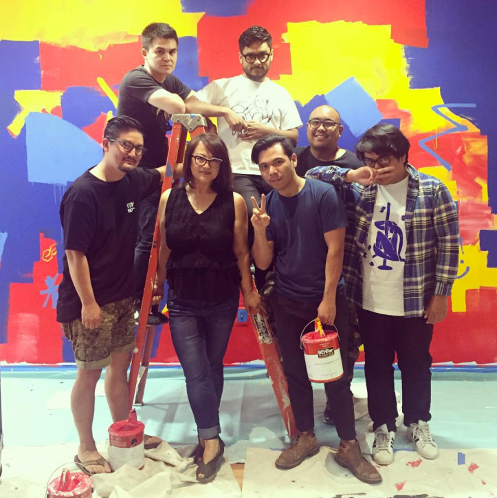 Installation of the exhibition, SECOND WAVE in progress, with Kristofferson San Pablo's wall mural in the background. Pictured are Jennifer Frias, curator of SECOND WAVE (center), along with some of the artists featured in the exhibition; (left to right) Devon Tsuno, Conrad Ruiz, Emilio Santoyo, Ryan Perez, Mark Batongmalaque and Kristofferson San Pablo. Photographs by Nikolay Maslov. Courtesy of UCR ARTSblock.