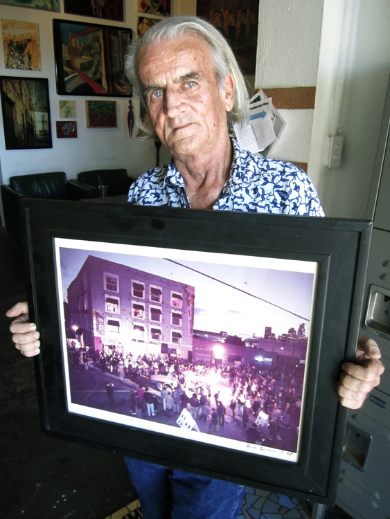 Terry Ellsworth with photograph of street party in front of Blooms General Store. Image courtesy of Patrick Quinn