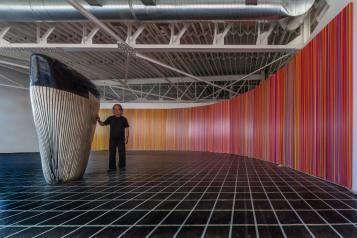 Jun Kaneko standing with Mirage (Studio Installation), 2016, acrylic on canvas, 9' x 63', and Untitled, Dango, 2016, hand built and glazed ceramic Photo by Takashi Hatakayama.