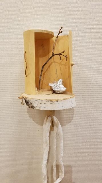 Saraswati- Snezana Petrovic Healing Earth Birch slice, wooden box, acupuncture needles, rock, Mogusa. Parallels: Medicine = Art. Crafton Hills College Art: Eyes on Healing. Crafton Hills College Art Gallery. Photo Credit Jacqueline Bell Johnson.
