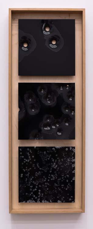 Caliber Abstractions. Nicolas Hunt. Photo Courtesy of Mugello Gallery. Bird, Buck, Slug: Black on Black #1 2017 43 inches x 16 inches oil based enamel on anodized aluminum and white oak.