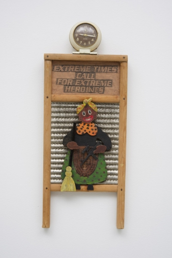 Betye Saar: Keeping it Clean. Craft and Folk Art Museum. Extreme Times Call for Extreme Heroines, 2017 Mixed media and wood figure on vintage washboard, clock Courtesy of the artist and Roberts & Tilton, Los Angeles, CA.