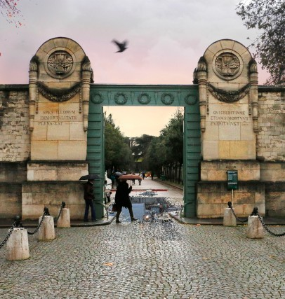 Main entrance to Père Lachaise Cemetery designed by neoclassic architect Etienne-Hippolyte Godde, the architect of the City of Paris from 1813-1830. The entrance design consists of a horseshoe–shaped driveway with a pair of tall central gates topped by two carved medallions or wreaths; a symbol of wisdom or victory over death, bearing the classic funerary symbols of the torch (life's flame) and the hourglass (time passing). Photo © Carolyn Campbell.